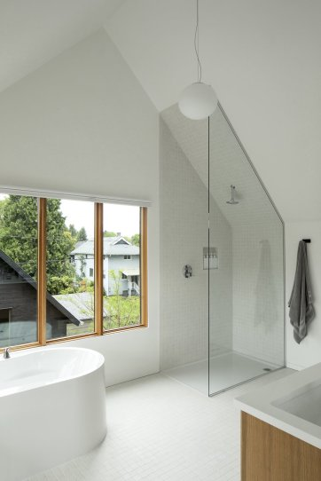 the-third-floor-master-bathroom-at-slender-house-enjoys-a-vaulted-ceiling-that-helps-create-a-sense-of-volume-and-spaciousnesseven-while-showering