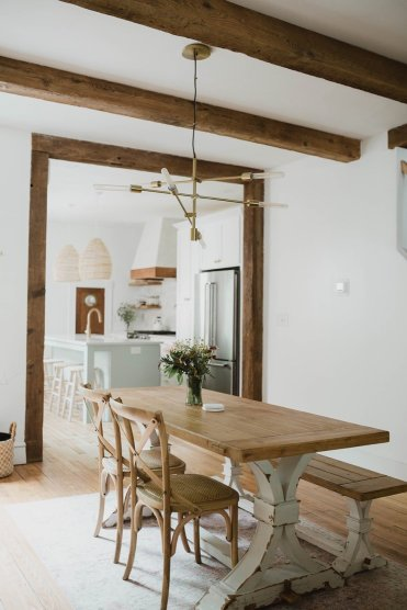 a-west-elm-light-fixture-hangs-over-the-dining-table-reclaimed-timber-ceiling-beams-and-trim-lend-a-sense-of-warmth-to-the-interior